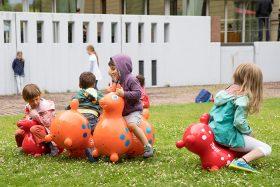 Vier Kinder reiten im Museumsgarten auf den im Text genannten Gummitieren