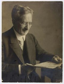 Schwarz-Weiß-Fotografie eines Mannes im Anzug und mit Brille, zeitungslesend an einem Tisch sitzend