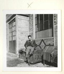 Ein junger Mann sitzt vor einem Haus (Schwarz-Weiß-Foto)
