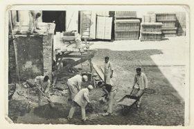 Sieben Männer in Arbeitskleidung und mit Schubkarre, Schaufeln und weiterem Arbeitsgerät (Schwarz-Weiß-Foto)