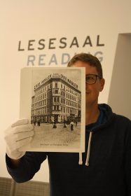 Jörg Waßmer hält eine Fotografie des ehemaligen Café Nagler in die Kamera