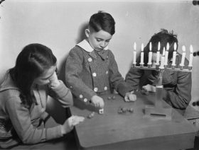 Black-and-white photograph showing two boys and a girl playing dreidel at a table. A Hanukkah menorah stands on the table with all of the candles lit.