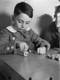 Schwarz-Weiß-Fotografie, die einen Jungen mit Dreidel an einem Tisch zeigt. Am Bildrand ist ein zweiter Junge zu sehen