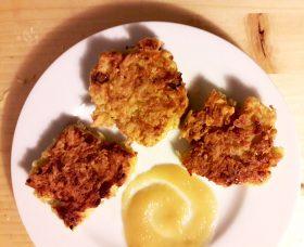 Das Bild zeigt drei Latkes auf einem Teller mit Apfelmus