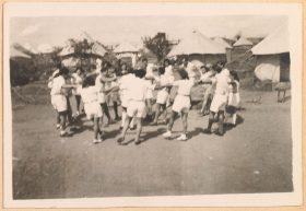Auf der Schwarzweiß-Fotografie tanzen Männer und Frauen in weißen Shorts und weißen Blusen, sich an den Händen haltend, mit dem jeweils linken Fuß ausholend, in einem inneren und einem äußeren Kreis. Im Hintergrunf sind weiße Zelte zu sehen.