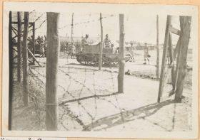 Im Vordergrund des Schwarzweiß-Fotos ist ein Stacheldrahtzaun zu sehen, der an Holzpfeilern befestigt ist. Im Hintergrund zwei Panzer, auf denen Soldaten sitzen, darum herum stehen vereinzelt Internierte.