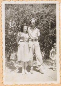 Auf dem schwarz-weiß Bild hält Walter Frankenstein seine Frau Leonie im Arm. Er trägt Militäruniform, sie ein Sommerkleid. Sie lächeln nicht. Am Bildrand ist, halbabgeschinittem einer ihrer Söhne zu sehen. Im Hintergrund wächst Buschwerk.