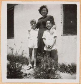 Auf der schwarz-weiß Fotografie legt Leonie im dunklen Kleid ihre Hände auf die Schultern der links und rechts stehenden und in weißen Shorts und Hemden gekleideten Kinder. Im Hintergrund ist eine Hauswand zu sehen.