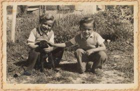 Auf dem schwarz-weiß Bild hocken die beiden Kinder in einem Garten und streicheln einen Hundewelpen.