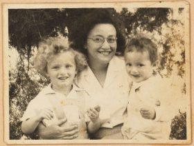 Schwarz-weiß Fotografie: Leonie sitzt in der Mitte und lächtelt breit. Auf ihrem Schoß sitzt Michael, der sich mit der Zunge über den rechten Mundwinkel fährt. Links steht Peter-Uri mit hellen Locken, ebenfalss breit lächelnd.