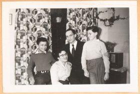 Auf dem schwarz-weiß Foto ist die Familie in einem Interieur der gemusterten Vorhängen und Zimmerpflanzen zu sehen. Alle vier lachen oder lächeln. Das Bild wirkt bewegt.