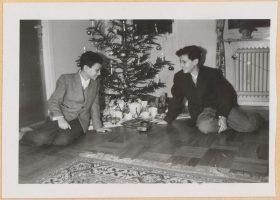 Auf dem schwarz-weiß Foto sitzen die beiden Jungen vor einem Weihnachtsbaum und blicken lachend auf die Gaben, die darunter drapiert sind.