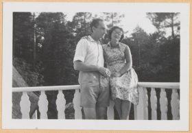 Auf dem schwarz-weiß Foto sitzt Leonie im Sommerkleid auf der Balkonbrüstung. Walter steht neben ihr, hat den linken Arm um sie gelegt und hält in der rechten Hand eine Zigarette.