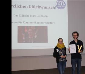 Unter einem Screen, auf dem das AK Volontariat den Gewinnern der Preisverleihung gratuliert, stehen Franziska und David, der die Urkunde und das Goldene V in die Kamera hält.
