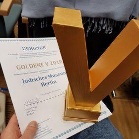 Auf dem Bild ist eine goldene v-förmige Trophäe in Nahaufnahme und die Urkunde zu sehen, auf der das Jüdische Museum Berlin als Gewinner der Auszeichnung vermerkt ist.