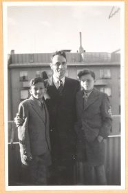 Auf dem schwarz-weiß Foto steht Rolf Rothschild steht in der Mitte und hat seine Arme um die beiden Jungen gelegt. Alle tragen Anzug.