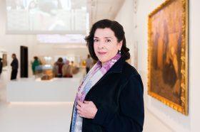 Auf dem Farbfoto ist Elene Bashkirova in schwarzem Blazer und violett gemustertem Schal zu sehen. Im Hintergrund ist die Jerusalem-Ausstellung des Jüdischen Museums Berlin zu erkennen.