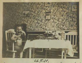 Ein Kleinkind sitzt auf einem Stuhl und lacht, neben ihm ein reich gedeckter Tisch.