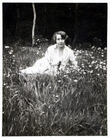 Schwarz-weiß-Fotogafie: Alice liegt in weißem Kleid und mit Kurzhaarschnitt auf einer Blumenwiese.