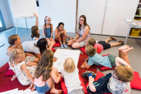 Ein knappes Dutzend Kinder sitzen und liegen im Kreis mit einer Erwachsenen. In der Mitte liegt ein Poster, auf dem u.a. »Familie« steht