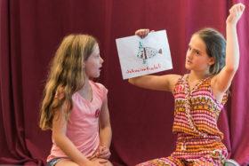 Zwei Mädchen, die rechte hält eine Zeichnung eines mit »Schweinefischili« beschrifteten Wesens hoch