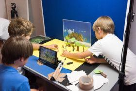 Drei Jungs vor einem iPad und einer gebastelten Filmkulisse bereiten die nächste Aufnahme vor