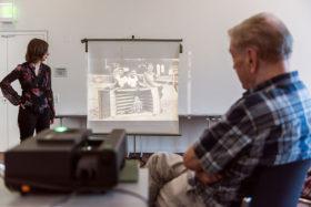 Ein Dia-Projektor wirft ein Schwarz-Weiß-Foto von vier Kindern und einem umgekippten Strandkorb auf eine Leinwand.