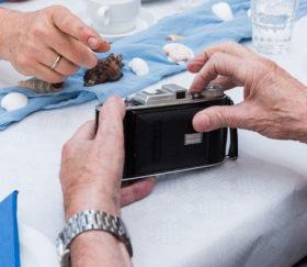 Hände hantieren mit einem alten Fotoapparat