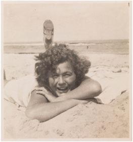 Schwarz-Weiß-Foto einer lockigen Frau am Strand, die auf dem Bauch im Sand liegt und einen beschuhten Fuß in den Himmel streckt