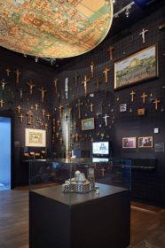 Ausstellungsraum mit vielen Kruzifixen an der Wand.