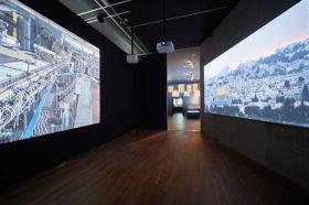 Ausstellungsraum mit zwei großen Leinwänden, auf denen Filme laufen