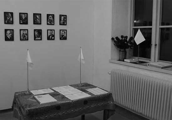 View of a room with a table, flags, portraits and a window.