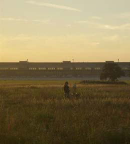 The painter with an easel in front of the main building at Tempelhof Airport at sunset