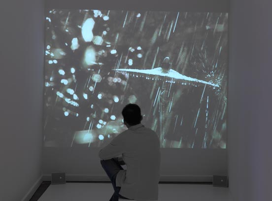 a visitor is sitting in front of a video projection