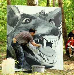 Man painting a wolf in a forest