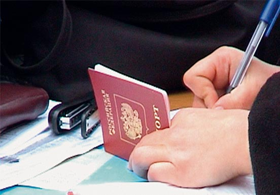 Hands holding a passport and pen