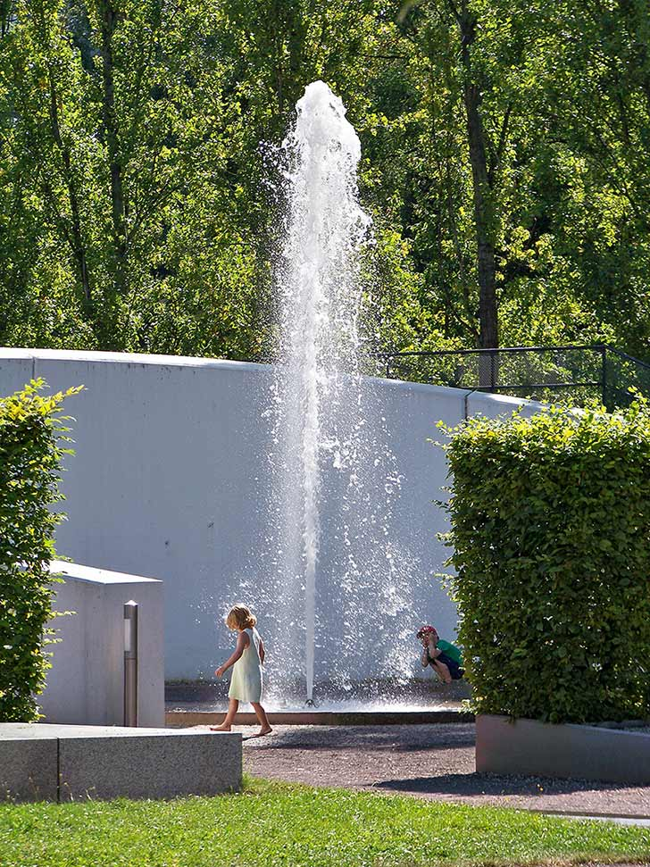 Water fountain in a garden, where a boy is squatting, in the foreground a girl in summer dress