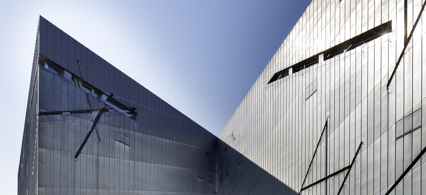 View of the zinc facade of the Libeskind Building against a blue sky (detail)