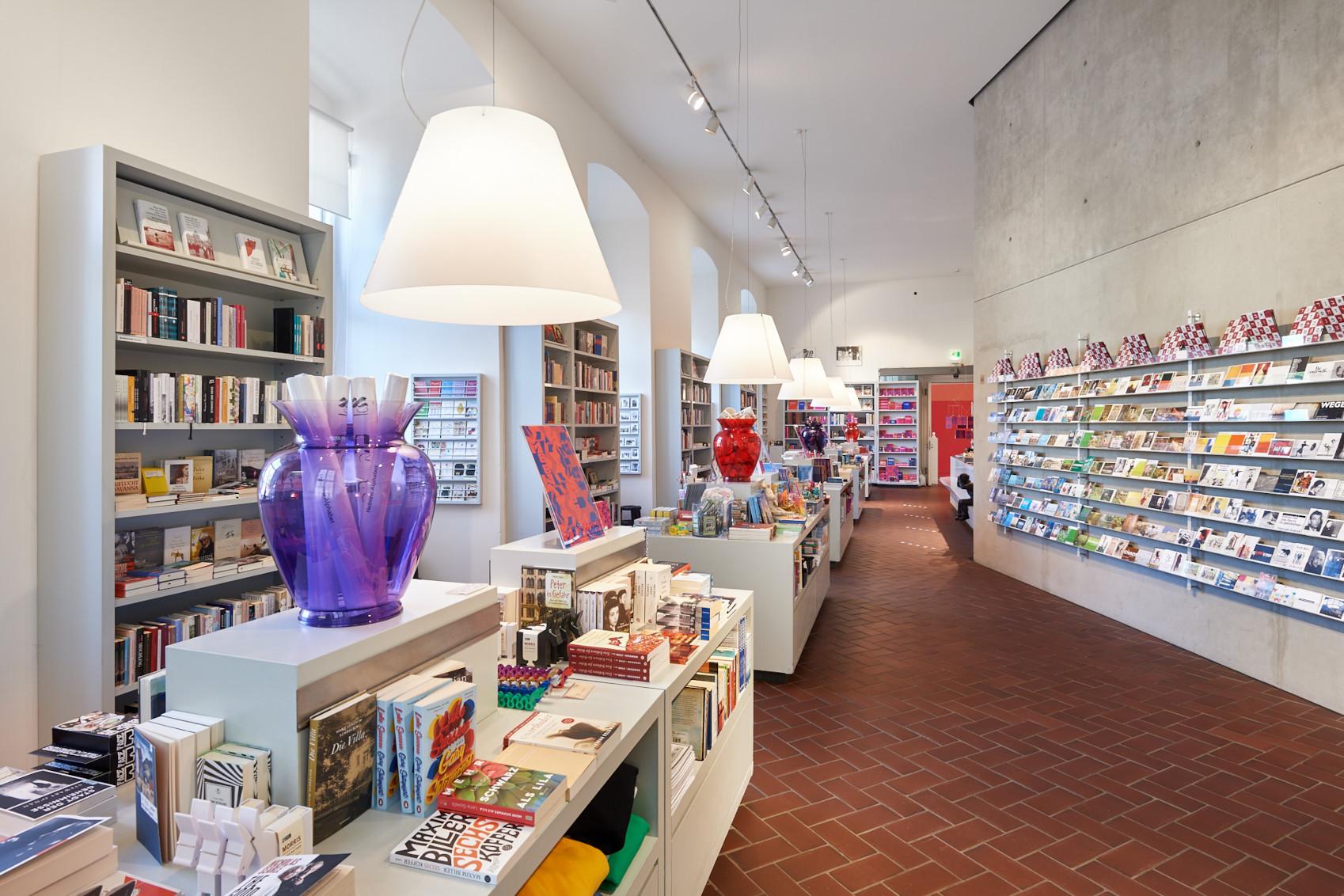 Blick in den Museumsshop; zu sehen sind Bücherregale, Vasen, die gerollt Poster enthalten sowie allerlei JMB-Artikel.