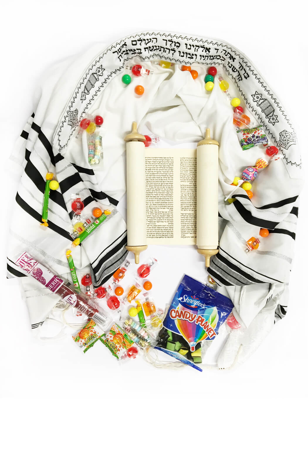 photo showing a tallit, a torah scroll, and candies