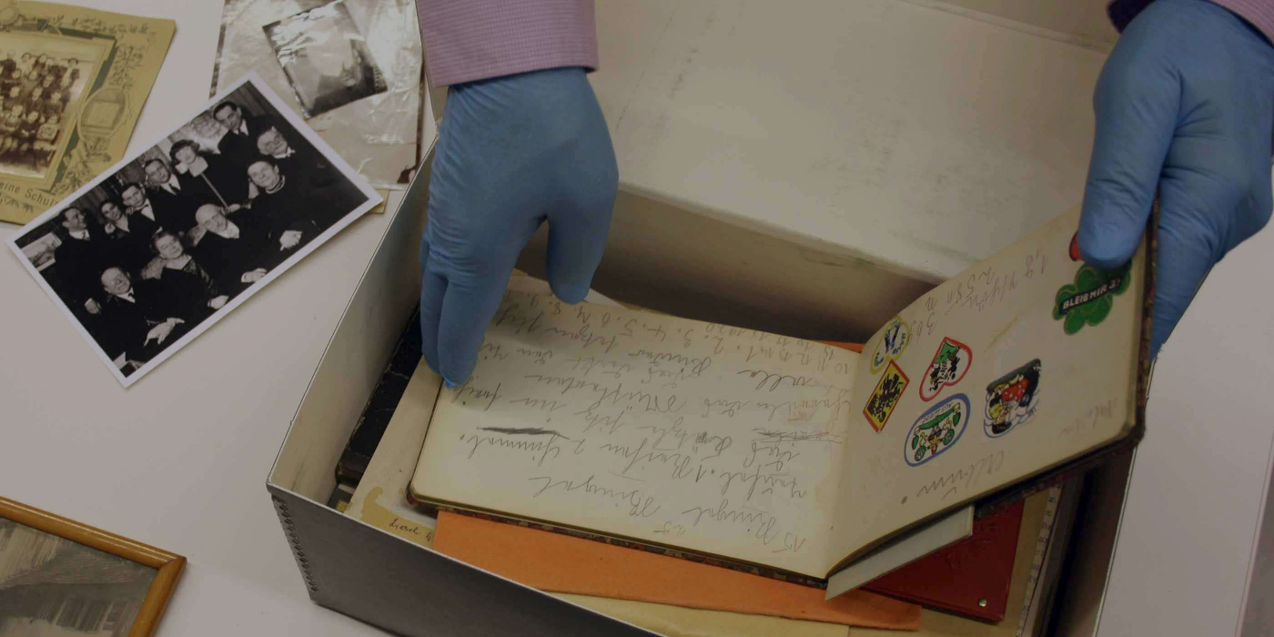 View from above into an opened box with documents. Two hands in archival gloves reach into the box and open the album that lies on top