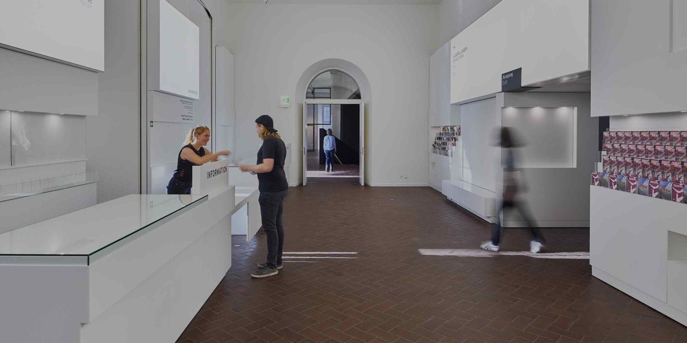 Blick ins Foyer, links der Infocounter, an dem zwei Personen stehen