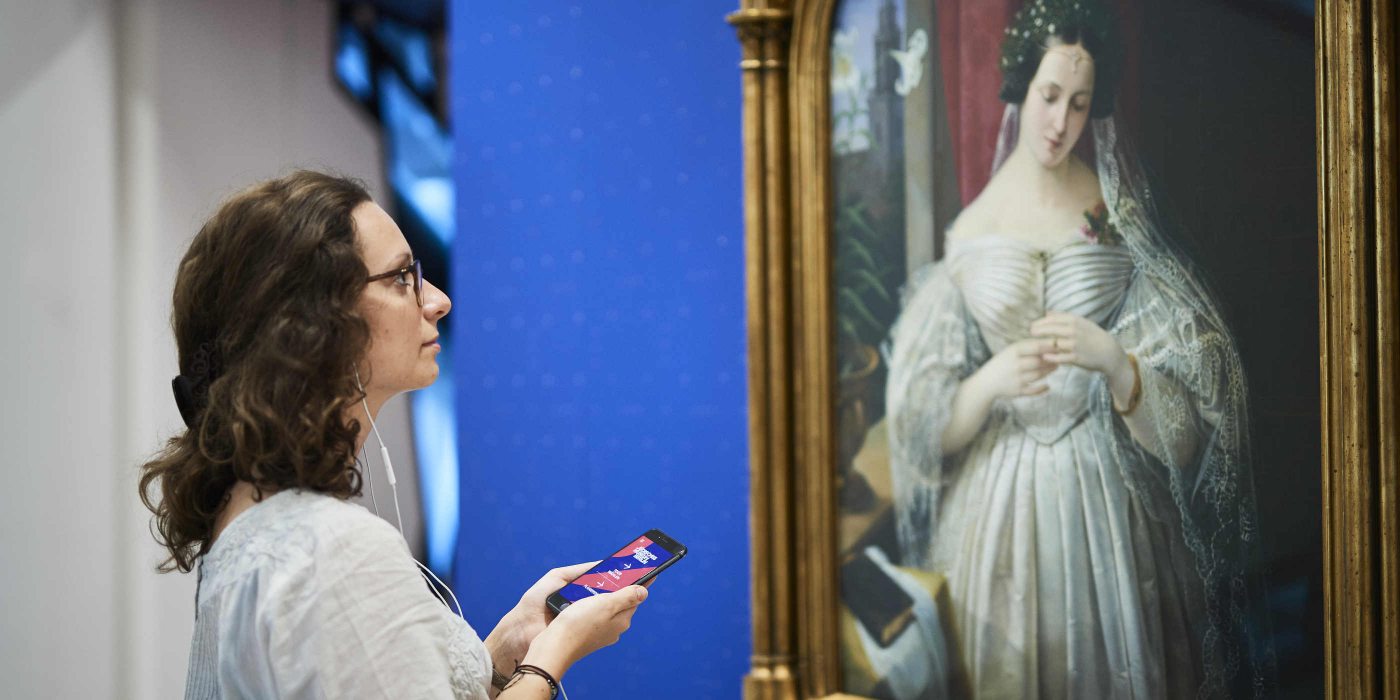 Young woman stands with smartphone and headphones in front of the portrait of Albertine Heine as bride of August Theodor Kaselowsky