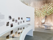 white room with display case with exhibits and photos on the wall