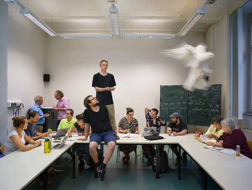 Students in a Talmud class look at texts or at each other while a white dove flies in the foreground of the picture