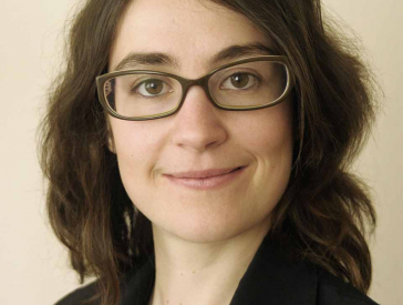 Portrait of a woman with glasses who smiles and looks directly into the camera