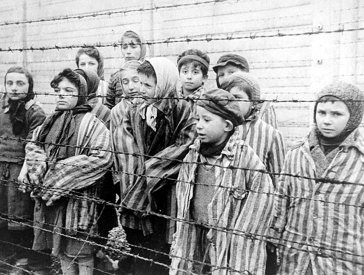 Black and white photograph with children in concentration camp clothes in Auschwitz standing behind barbed wire fence