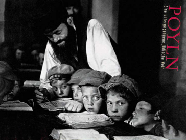 The black and white photo shows several boys in caps sitting close together at a table. In front of them are open books, behind them stands a man and points to a line of text