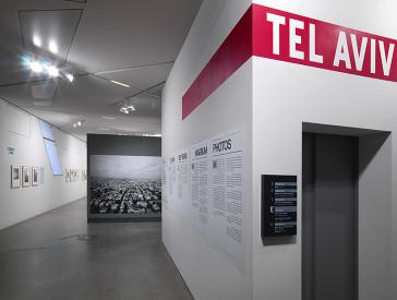 Blick in den Eingangsbereich der Ausstellung: Rechts eine Wand mit Beschriftung, im Hintergrund ein großen Schwarz-Weiß-Foto, das ein Lufbild einer Großstadt zeigt