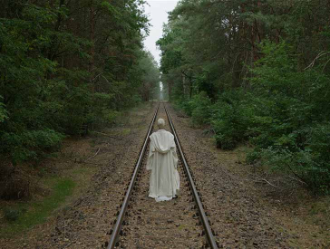 The photo shows a person from behind, dressed in a white frock. The person follows railroad tracks that run dead straight through a forest